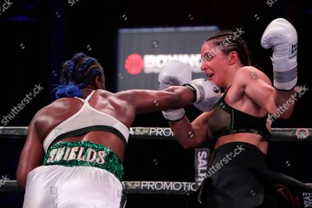 Claressa Shields, left, fights Christina Hammer during the fifth round of a women's unification world middleweight championship bout, in Atlantic City, N.J