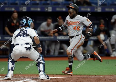 Dwight Smith Jr., Michael Perez. Baltimore Orioles' Dwight Smith Jr., right, scores ahead of the throw to Tampa Bay Rays catcher Michael Perez on a double by Renato Nunez during the third inning of a baseball game, in St. Petersburg, Fla