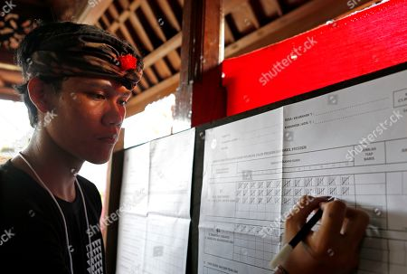 "An electoral worker checks a vote for presidential candidate Joko ""Jokowi"" Widodo during the vote counting at a polling station in Bali, Indonesia on . Tens of millions of Indonesians voted in presidential and legislative elections Wednesday after a campaign that pitted the moderate incumbent against an ultranationalist former general whose fear-based rhetoric warned that the country would fall apart without his strongman leadership"