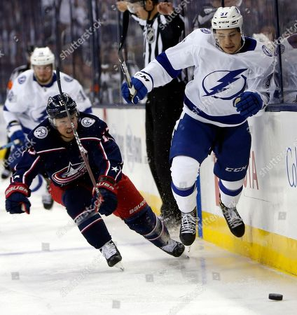 Columbus Blue Jackets' Cam Atkinson, left, and Tampa Bay Lightning's Yanni Gourde chase a loose puck during the third period of Game 4 of an NHL hockey first-round playoff series, in Columbus, Ohio. The Blue Jackets beat the Lightning 7-3