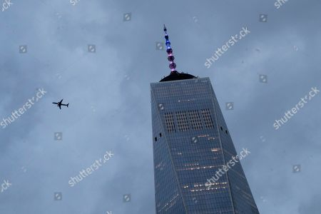 A airplane flies past the lit spire of One World Trade Center, in New York. New York Governor Andrew M. Cuomo has directed that One World Trade Center's spire be lighted in the colors of the French flag in solidarity with the people of France and the Catholic community worldwide
