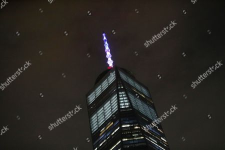 Stock Photo of The spire of One World Trade Center is lit, in New York. New York Governor Andrew M. Cuomo has directed that One World Trade Center's spire be lighted in the colors of the French flag in solidarity with the people of France and the Catholic community worldwide