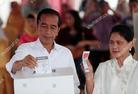 "Indonesian President Joko ""Jokowi"" Widodo and his wife Iriana cast their ballots during the election at a polling station in Jakarta, Indonesia, . Tens of millions of Indonesians were voting in presidential and legislative elections Wednesday after a campaign that pitted the moderate incumbent against an ultranationalist former general whose fear-based rhetoric warned the country would fall apart without his strongman leadership"