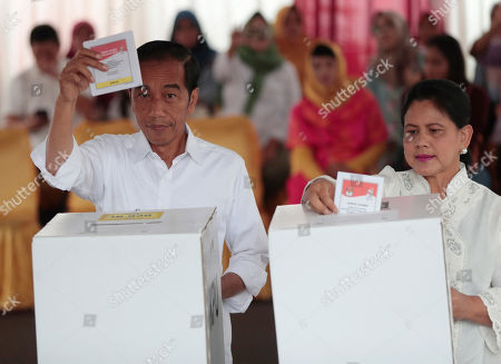 "Joko Widodo. Indonesian President Joko ""Jokowi"" Widodo and his wife Iriana cast their ballots during the election at a polling station in Jakarta, Indonesia, . Tens of millions of Indonesians were voting in presidential and legislative elections Wednesday after a campaign that pitted the moderate incumbent against an ultranationalist former general whose fear-based rhetoric warned the country would fall apart without his strongman leadership"