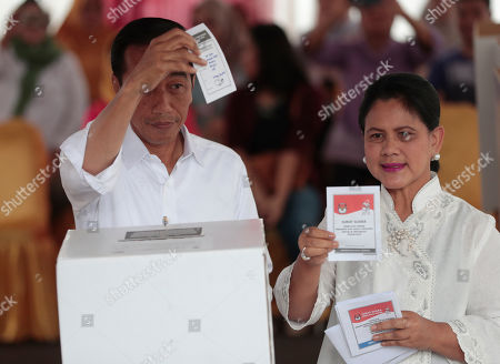 "Joko Widodo. Indonesian President Joko ""Jokowi"" Widodo and his wife Iriana show their ballots during the election at a polling station in Jakarta, Indonesia, . Tens of millions of Indonesians were voting in presidential and legislative elections Wednesday after a campaign that pitted the moderate incumbent against an ultranationalist former general whose fear-based rhetoric warned the country would fall apart without his strongman leadership"