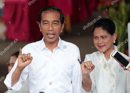 "Indonesian President Joko ""Jokowi"" Widodo and wife Iriana show their inked fingers after casting their ballots during the election at a polling station in Jakarta, Indonesia, . Tens of millions of Indonesians were voting in presidential and legislative elections Wednesday after a campaign that pitted the moderate incumbent against an ultranationalist former general whose fear-based rhetoric warned the country would fall apart without his strongman leadership"