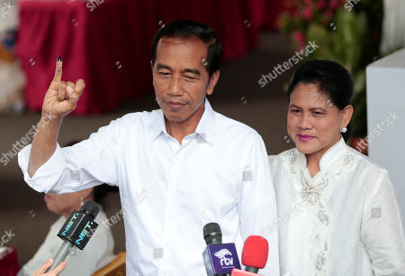"Indonesian President Joko ""Jokowi"" Widodo, left, show his inked finger as his wife Iriana looks on after casting their ballots during the election at a polling station in Jakarta, Indonesia, . Tens of millions of Indonesians were voting in presidential and legislative elections Wednesday after a campaign that pitted the moderate incumbent against an ultranationalist former general whose fear-based rhetoric warned the country would fall apart without his strongman leadership"