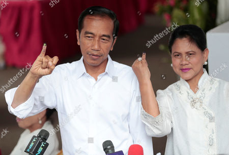 "Indonesian President Joko ""Jokowi"" Widodo and his wife Iriana show their inked finger after casting their ballots during the election at a polling station in Jakarta, Indonesia, . Tens of millions of Indonesians were voting in presidential and legislative elections Wednesday after a campaign that pitted the moderate incumbent against an ultranationalist former general whose fear-based rhetoric warned the country would fall apart without his strongman leadership"