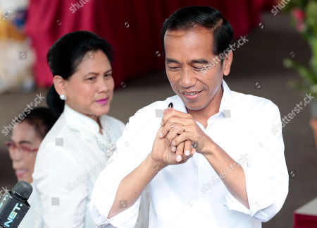"Indonesian President Joko ""Jokowi"" Widodo shows his inked finger as his wife Iriana looks on after casting their ballots during the election at a polling station in Jakarta, Indonesia, . Tens of millions of Indonesians were voting in presidential and legislative elections Wednesday after a campaign that pitted the moderate incumbent against an ultranationalist former general whose fear-based rhetoric warned the country would fall apart without his strongman leadership"
