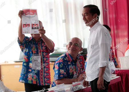 "Indonesian President Joko ""Jokowi"" Widodo, right, looks on as an electoral worker shows a presidential ballot during the election at a polling station in Jakarta, Indonesia, . Tens of millions of Indonesians were voting in presidential and legislative elections Wednesday after a campaign that pitted the moderate incumbent against an ultranationalist former general whose fear-based rhetoric warned the country would fall apart without his strongman leadership"