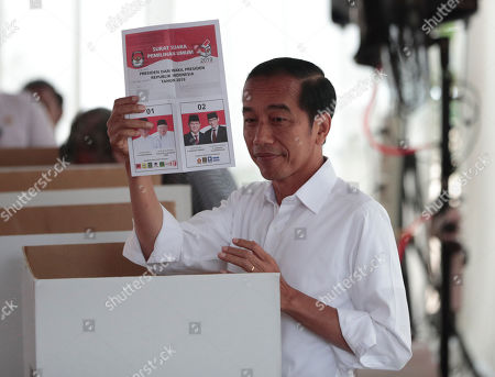 "Indonesian President Joko ""Jokowi"" Widodo shows his ballot before voting at a polling station in Jakarta, Indonesia, . Tens of millions of Indonesians were voting in presidential and legislative elections Wednesday after a campaign that pitted the moderate incumbent against an ultranationalist former general whose fear-based rhetoric warned the country would fall apart without his strongman leadership"