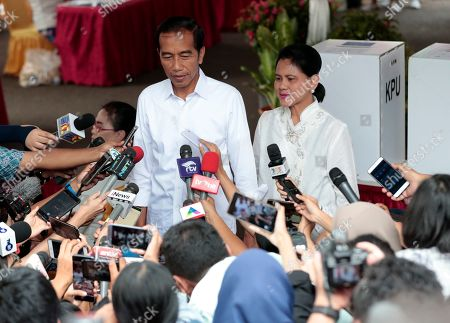 "Indonesian President Joko ""Jokowi"" Widodo answers reporters' questions as his wife Iriana looks on after casting their ballots during the election at a polling station in Jakarta, Indonesia, . Tens of millions of Indonesians were voting in presidential and legislative elections Wednesday after a campaign that pitted the moderate incumbent against an ultranationalist former general whose fear-based rhetoric warned the country would fall apart without his strongman leadership"