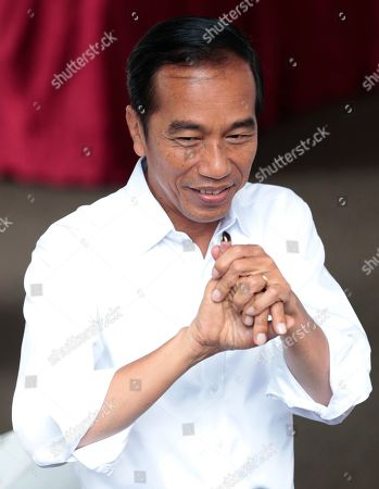 "Indonesian President Joko ""Jokowi"" Widodo shows his inked finger after casting his ballots during the election at a polling station in Jakarta, Indonesia, . Tens of millions of Indonesians were voting in presidential and legislative elections Wednesday after a campaign that pitted the moderate incumbent against an ultranationalist former general whose fear-based rhetoric warned the country would fall apart without his strongman leadership"