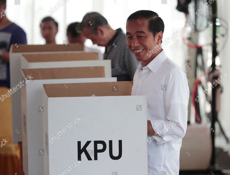 "Indonesian President Joko ""Jokowi"" Widodo smiles as he votes during the election at a polling station in Jakarta, Indonesia, . Tens of millions of Indonesians were voting in presidential and legislative elections Wednesday after a campaign that pitted the moderate incumbent against an ultranationalist former general whose fear-based rhetoric warned the country would fall apart without his strongman leadership"