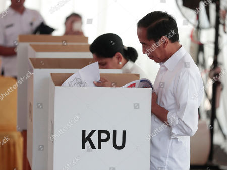 "Indonesian President Joko ""Jokowi"" Widodo, right, and his wife Iriana give their votes during the election at a polling station in Jakarta, Indonesia, . Tens of millions of Indonesians were voting in presidential and legislative elections Wednesday after a campaign that pitted the moderate incumbent against an ultranationalist former general whose fear-based rhetoric warned the country would fall apart without his strongman leadership"