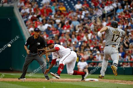 Washington Nationals first baseman Howie Kendrick, center, reaches for a throw as Pittsburgh Pirates' JB Shuck runs toward first base during a baseball game, in Washington