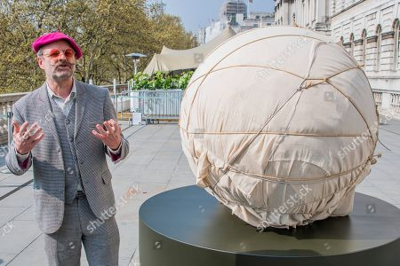 Gavin Turk with his sculpture before being unwrapped
