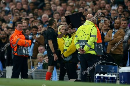 Turkish referee Cuneyt Cakir reviews the VAR before giving a goal to Tottenham's Fernando Llorente during the Champions League quarterfinal, second leg, soccer match between Manchester City and Tottenham Hotspur at the Etihad Stadium in Manchester, England