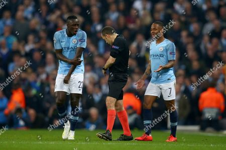 Turkish referee Cuneyt Cakir walks away after reviewing the VAR and giving a goal to Tottenham's Fernando Llorente as Manchester City's Benjamin Mendy and Manchester City's Raheem Sterling continue to appeal for handball during the Champions League quarterfinal, second leg, soccer match between Manchester City and Tottenham Hotspur at the Etihad Stadium in Manchester, England