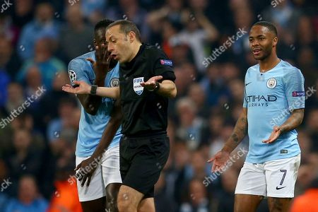 Turkish referee Cuneyt Cakir walks away after reviewing the VAR and giving a goal to Tottenham's Fernando Llorente as Manchester City's Benjamin Mendy, left, and Manchester City's Raheem Sterling, 7, continue to appeal for handball during the Champions League quarterfinal, second leg, soccer match between Manchester City and Tottenham Hotspur at the Etihad Stadium in Manchester, England