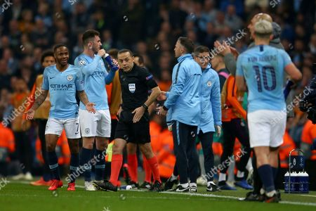 Turkish referee Cuneyt Cakir, center, walks away after reviewing the VAR and giving a goal to Tottenham's Fernando Llorente as Manchester City's Raheem Sterling, left, Manchester City's Sergio Aguero, 10, and Manchester City coach Pep Guardiola, in front of Aguero react, during the Champions League quarterfinal, second leg, soccer match between Manchester City and Tottenham Hotspur at the Etihad Stadium in Manchester, England