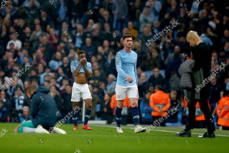 Manchester City's Raheem Sterling, second left, and Manchester City coach Pep Guardiola, right, react after being defeated in the Champions League quarterfinal, second leg, soccer match between Manchester City and Tottenham Hotspur at the Etihad Stadium in Manchester, England