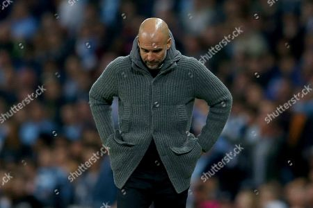 Manchester City coach Pep Guardiola looks down during the Champions League quarterfinal, second leg, soccer match between Manchester City and Tottenham Hotspur at the Etihad Stadium in Manchester, England