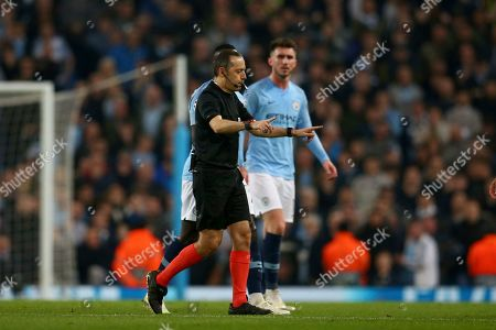 Turkish referee Cuneyt Cakir calls for a VAR review from which he gave a goal to Tottenham's Fernando Llorente during the Champions League quarterfinal, second leg, soccer match between Manchester City and Tottenham Hotspur at the Etihad Stadium in Manchester, England