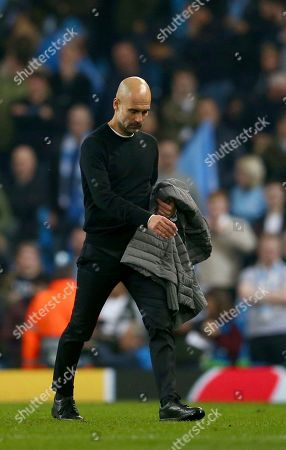Manchester City coach Pep Guardiola walks off the pitch after being defeated in the Champions League quarterfinal, second leg, soccer match between Manchester City and Tottenham Hotspur at the Etihad Stadium in Manchester, England