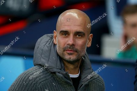 Manchester City coach Pep Guardiola waits for the start of the Champions League quarterfinal, second leg, soccer match between Manchester City and Tottenham Hotspur at the Etihad Stadium in Manchester, England