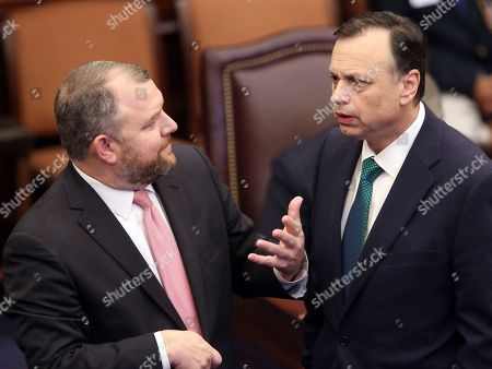 Sen. Roy Bradley, R-Fleming Island, left, confers with Sen. Tom Lee, R-Brandon during the debate on a bill to allow teachers to be armed during session, in Tallahassee, Fla