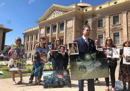Brendan Lyons, director of the group Look! Save a Life, foreground, stands with relatives of people who have been killed by distracted drivers at the state Capitol in Phoenix on . Arizona House lawmakers will get to choose between three proposed laws that are designed to deal with distracted driving caused by cell phone use, Speaker Rusty Bowers announced after a closed-door meeting of majority Republicans Wednesday