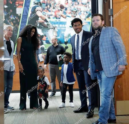 Seattle Seahawks NFL football quarterback Russell Wilson, second from right, arrives for a press conference with his wife Ciara, their daughter Sienna, and Ciara's son Future, along with head coach Pete Carroll, left, and general manager John Schneider, right, in Renton, Wash. Earlier in the week, Wilson signed a $140 million, four-year extension with the team
