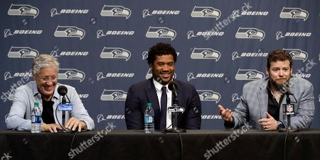 Seattle Seahawks NFL football quarterback Russell Wilson, center, talks to reporters along with head coach Pete Carroll, left, and general manager John Schneider, right, in Renton, Wash. Earlier in the week, Wilson signed a $140 million, four-year extension with the team