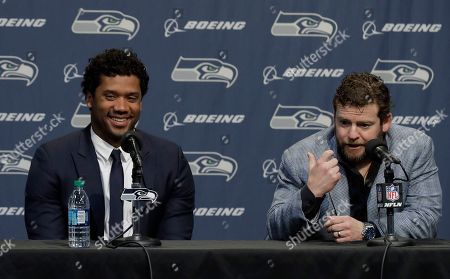 Seattle Seahawks quarterback Russell Wilson, left, talks to reporters along with general manager John Schneider, right, in Renton, Wash. Earlier in the week, Wilson signed a $140 million, four-year extension with the NFL football team