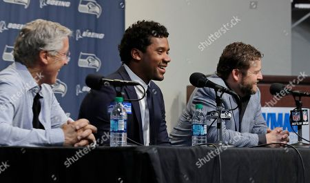 Seattle Seahawks quarterback Russell Wilson, center, talks to reporters along with coach Pete Carroll, left, and general manager John Schneider, right, in Renton, Wash. Earlier in the week, Wilson signed a $140 million, four-year extension with the NFL football team
