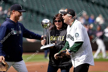 Seattle Mariners manager Scott Servais, left, greets Seattle Storm head coach Dan Hughes, right, and Hughes' wife, Mary Hughes, after Dan Hughes tossed out the ceremonial first pitch to Servias before a baseball game against the Cleveland Indians, in Seattle. Mary Hughes held the WNBA championship trophy the team earned last season