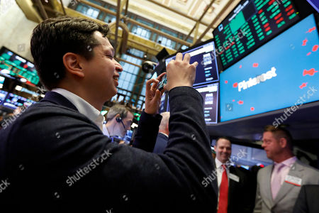 Pinterest co-founder & CEO Ben Silbermann uses his mobile phone to photograph on the the New York Stock Exchange trading floor, before the Pinterest IPO
