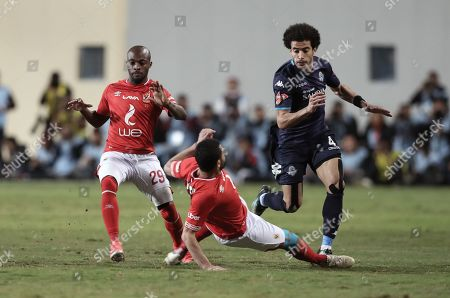Al-Ahly player Ahmed Fathy (C)  and Gelardo (L) in action against  Pyramids player Omar Gaber (R) during the Egyptian League soccer match between Al-Ahly and Pyramids in Cairo, Egypt, 18 April 2019.