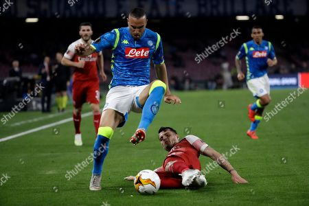 Arsenal's Granit Xhaka, bottom, tries to stop Napoli's Arkadiusz Milik during the Europa League second leg quarterfinal soccer match between Napoli and Arsenal at San Paolo stadium in Naples, Italy