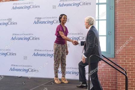 Christine Pusey, Jamie Dimon. Christine Pusey, left, shakes hands with Jamie Dimon, Chairman and CEO, JPMorgan Chase, as he takes the stage to announce that Louisville is one of five winning cities in its inaugural AdvancingCities Challenge, at the Kentucky Center for African American Heritage in Louisville, Ky. Pusey, a Louisville resident, was a beneficiary of Goodwill Industries of Kentucky's Cars To Work program, a partner in Metro United Way of Louisville's partners in the winning proposal addressing jobs, skills and financial health