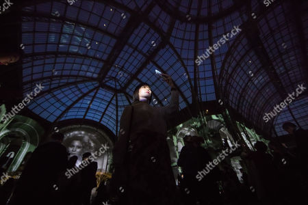Visitors look at a projection of the German director Wim Wenders, a monumental cinematographic installation based on his entire film work, projected on the interior structure of the Nave of the Grand Palais in Paris, France, 18 April 2019. The exhibition will run from 18 to 22 April 2019.