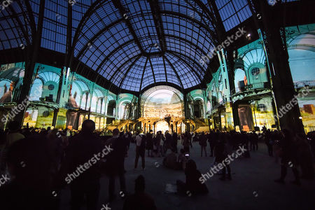 Stock Picture of Visitors look at a projection of the German director Wim Wenders, a monumental cinematographic installation based on his entire film work, projected on the interior structure of the Nave of the Grand Palais in Paris, France, 18 April 2019. The exhibition will run from 18 to 22 April 2019.