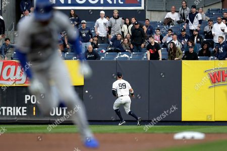 New York Yankees right fielder Aaron Judge (99) fields a ball off the wall hit by Kansas City Royals' Alex Gordon, as Royals' Adalberto Mondesi, left, runs to third base during the first inning of a baseball game, in New York. Mondesi scored on the play