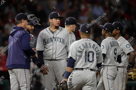 Felix Hernandez, Paul Davis. Seattle Mariners gather at the mound as starting pitcher Felix Hernandez, third from left, is relieved by manager Scott Servais during the seventh inning of the team's baseball game against the Los Angeles Angels, in Anaheim, Calif