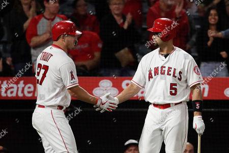 Mike Trout, Albert Pujols. Los Angeles Angels' Mike Trout, left, shakes hands with Albert Pujols after scoring on a double hit by Andrelton Simmons during the seventh inning of a baseball game against the Seattle Mariners, in Anaheim, Calif