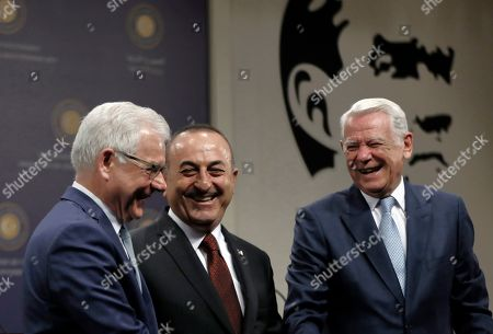 Mevlut Cavusoglu, Jacek Czaputowicz, Teodor Melescanu. Turkish Foreign Minister Mevlut Cavusoglu, centre, Polish Foreign Minister Jacek Czaputowicz, left, and Romanian Foreign Minister Teodor Melescanu smile after a joint news conference following a meeting of political-military consultations between the NATO countries, in Ankara, Turkey