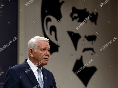 Stock Image of Backdropped by an image of Turkey's founder Mustafa Kemal Ataturk, Romanian Foreign Minister Teodor Melescanu speaks to the media after a meeting of political-military consultations between the NATO countries with Turkish Foreign Minister Mevlut Cavusoglu and Polish Foreign Minister Jacek Czaputowicz, in Ankara, Turkey