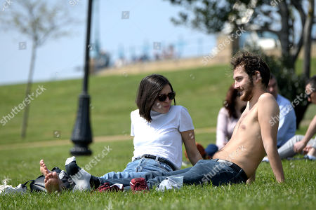 Stock Image of Visitors enjoy a very warm Good Friday by taking to novelty boats and relaxing in the sun in the park and gardens at Alexandra Palace, North London.