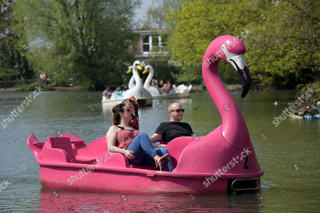 Stock Picture of Visitors enjoy a very warm Good Friday by taking to novelty boats and relaxing in the sun in the park and gardens at Alexandra Palace, North London.